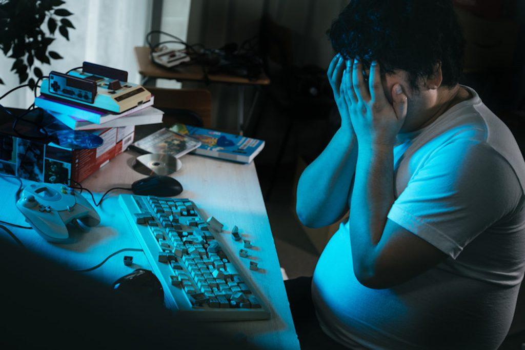 ボロボロのキーボードと絶望する男性