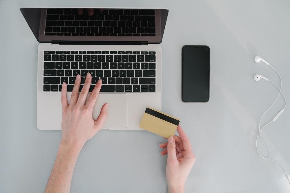 パソコンのキーボードとクレカに触れる人